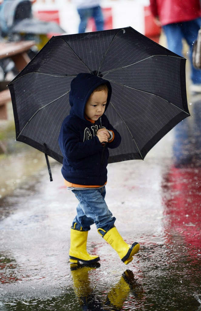 Eric Buehler, 3, of Boxford, Mass., is ready for the weather with an umbrella and bright rain boots at the Fryeburg Fair.