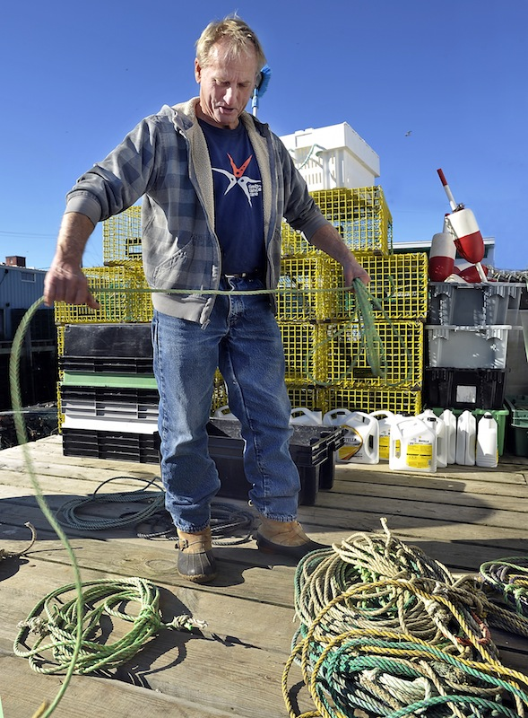 """Lobsterman Jim Holden, working on Widgery Wharf in Portland on Thursday, prepares to move his traps into deeper water in advance of next week's arrival of Hurricane Sandy. """"I think I lost 300 traps"""" during the """"perfect storm"""" of 1991, he said. """"I hope I don't get bit that bad again."""""""