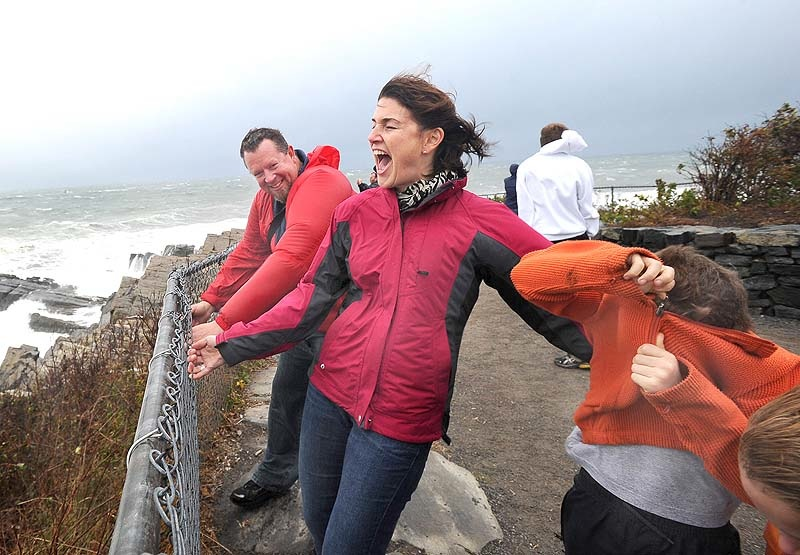 Michael and Kristin Guibord from Portland grab a fence and their two boys Orion 8 and Jonah 6 as they brace against the wind to view Portland Head Light in Cape Elizabeth on Mon. Oct. 29, 2012.