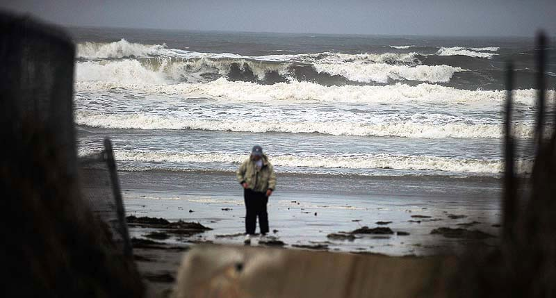 Diane Visch of Scarborough heads back home Tuesday morning, after checking out the heavy surf at Higgins Beach kicked up by Hurricane Sandy.