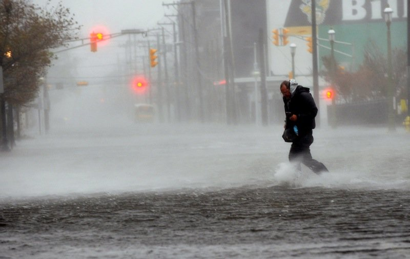 Michael Wirtz, of Wilmington, Del., braves flood waters and high winds that arrive with Hurricane Sandy along North Michigan Avenue in Atlantic City, N.J., on Monday. Hurricane Sandy continued on its path Monday, forcing the shutdown of mass transit, schools and financial markets, sending coastal residents fleeing for higher ground, and threatening a dangerous mix of high winds and soaking rain.