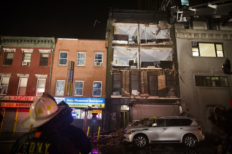 Firefighters look up at the facade of a four-story building on 14th Street and 8th Avenue that collapsed onto the sidewalk Monday, Oct. 29, 2012, in New York. Hurricane Sandy bore down on the Eastern Seaboard's largest cities Monday, forcing the shutdown of mass transit, schools and financial markets, sending coastal residents fleeing, and threatening a dangerous mix of high winds, soaking rain and a surging wall of water up to 11 feet tall. (AP Photo/ John Minchillo)