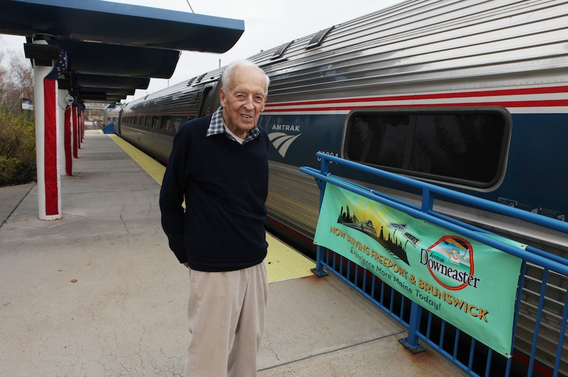 Nelson Soule, 91, poses next to the Amtrak Downeaster train Wednesday, Oct. 31, 2012 at the station in Portland, Maine. Soule will be aboard Amtrak's Downeaster on Thursday as the Boston-to-Portland service expands northward to Freeport and Brunswick for the first time in more than 50 years. (AP Photo/Joel Page)