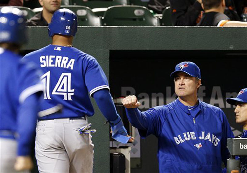 Toronto Blue Jays manager John Farrell, right, fist bumps Moises Sierra after Sierra scored a run on a sacrifice fly by J.P. Arencibia in the second inning of the second baseball game of a doubleheader against the Baltimore Orioles in Baltimore, Monday, Sept. 24, 2012. (AP Photo/Patrick Semansky)
