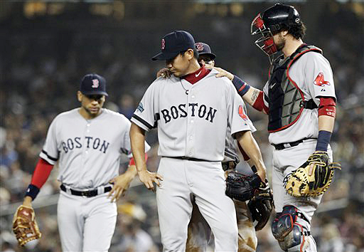 Teammates console starting pitcher Daisuke Matsuzaka, center, before Matsuzaka was pulled during the third inning of the Red Sox game against the New York Yankees on Wednesday.