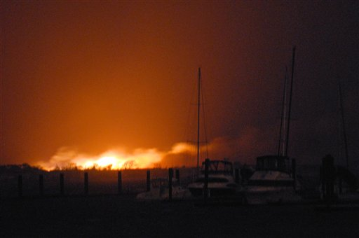 A fire burns at least two dozen homes in a flooded neighborhood in the New York City borough of Queens on Tuesday. A fire department spokesman says more than 190 firefighters are at the blaze in the Breezy Point section. Fire officials say the blaze was reported around 11 p.m. Monday in an area flooded by the superstorm that began sweeping through earlier.