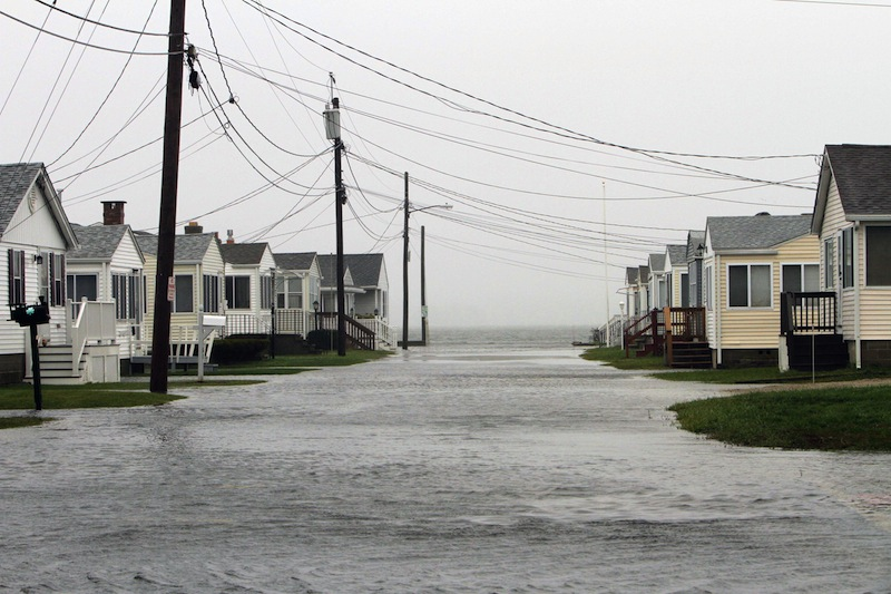 The high tide floods streets, Monday, Oct. 29, 2012 from the effects of Hurricane Sandy in Hampton, N.H. Hurricane Sandy continued on its path Monday, as the storm forced the shutdown of mass transit, schools and financial markets, sending coastal residents fleeing, and threatening a dangerous mix of high winds and soaking rain. (AP Photo/Jim Cole)
