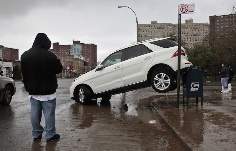 The tailend of a SUV is perched on top of a postal mailbox in the aftermath of floods from Hurricane Sandy on Tuesday, Oct. 30, 2012, in Coney Island, N.Y. Maine didn't suffer nearly as bad of damage as other parts of country like New York and New Jersey, which were overrun with water and suffered billions in damage. (AP Photo/Bebeto Matthews)