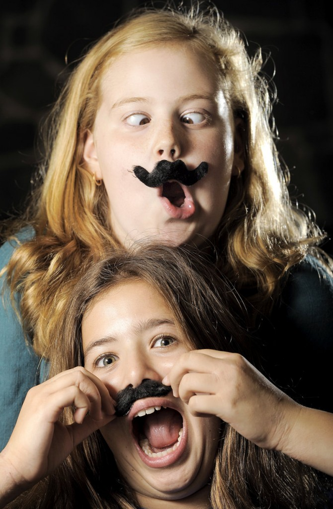 Sarah Rabinowitz, top, and Sydney Pearl, sixth-graders at Falmouth Middle School, are heavily into the mustache craze and say they regularly wear fake staches to school. They own T-shirts, magnets, wallets, duct tape and other items with a mustache theme.