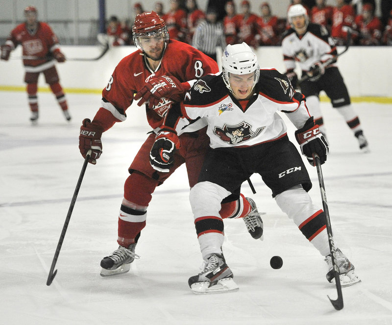 Phil Lane of the Pirates tries to control the puck against Antoine-Houde Caron of the University of New Brunswick.