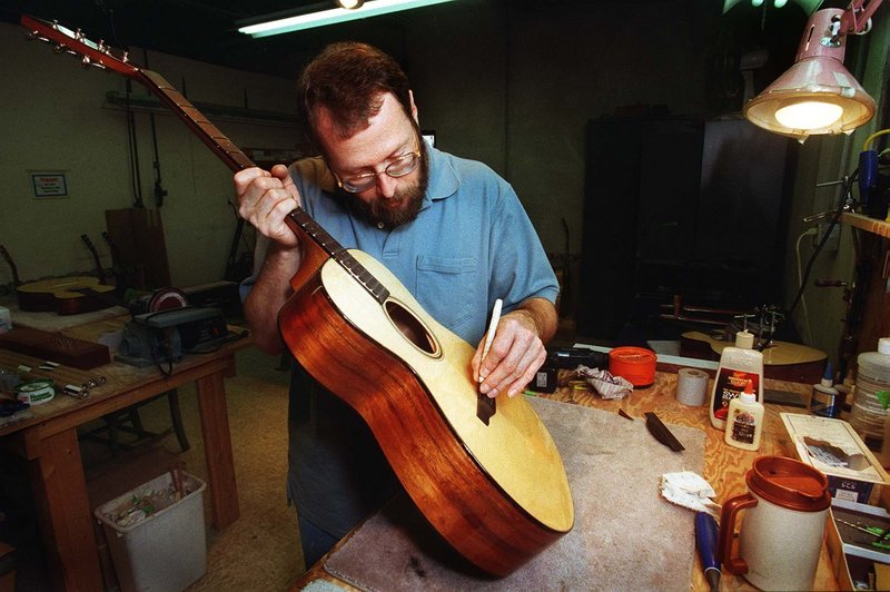 Dana Bourgeois of Lewiston works on a guitar in 2001, when his guitar shop was featured in a story in the Maine Sunday Telegram. The Bourgeois team is still on the cutting edge in the world of guitar-making.
