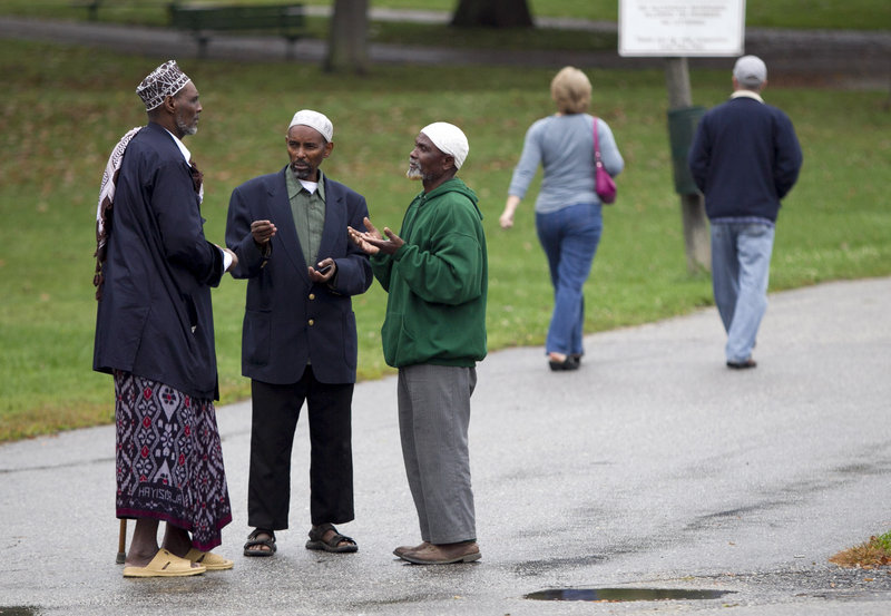 Somali men talk in Lewiston on Thursday. From 2000 to 2010, the city's African-American population grew from 383 to 3,174, an increase of 828 percent. City officials say the number is perhaps as high as 6,000 today.