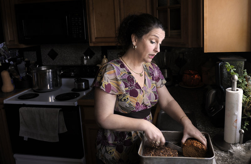 Catherine Lewis slices a piece of banana bread with marijuana as an ingredient for her husband, Glenn, at their Manchester home.