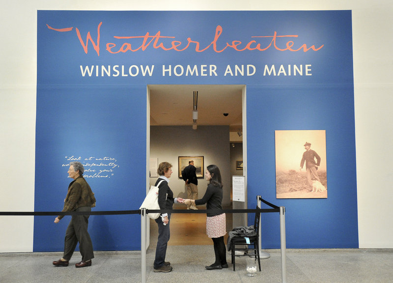Anna Schember, right, collects a ticket Friday from one of the estimated 75,000 people who are expected to visit the Winslow Homer exhibition at the Portland Museum of Art.