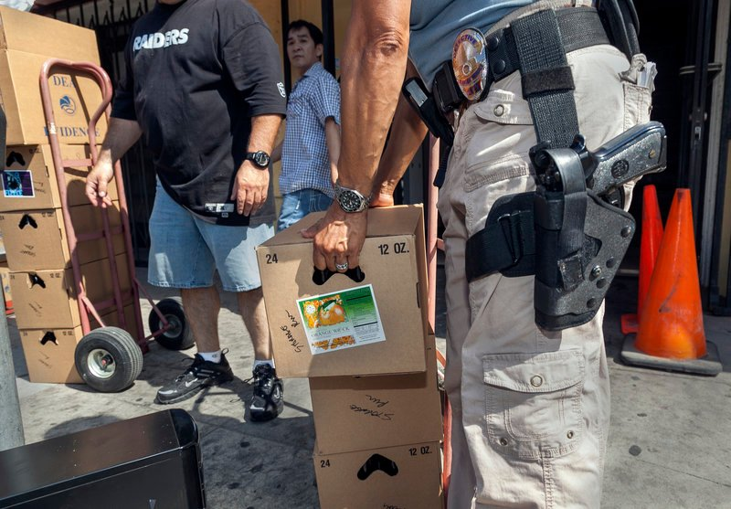 Los Angeles police officers assist Drug Enforcement Administration agents serving a federal warrant to shut down a marijuana dispensary operating in the Chinatown area of Los Angeles last month.