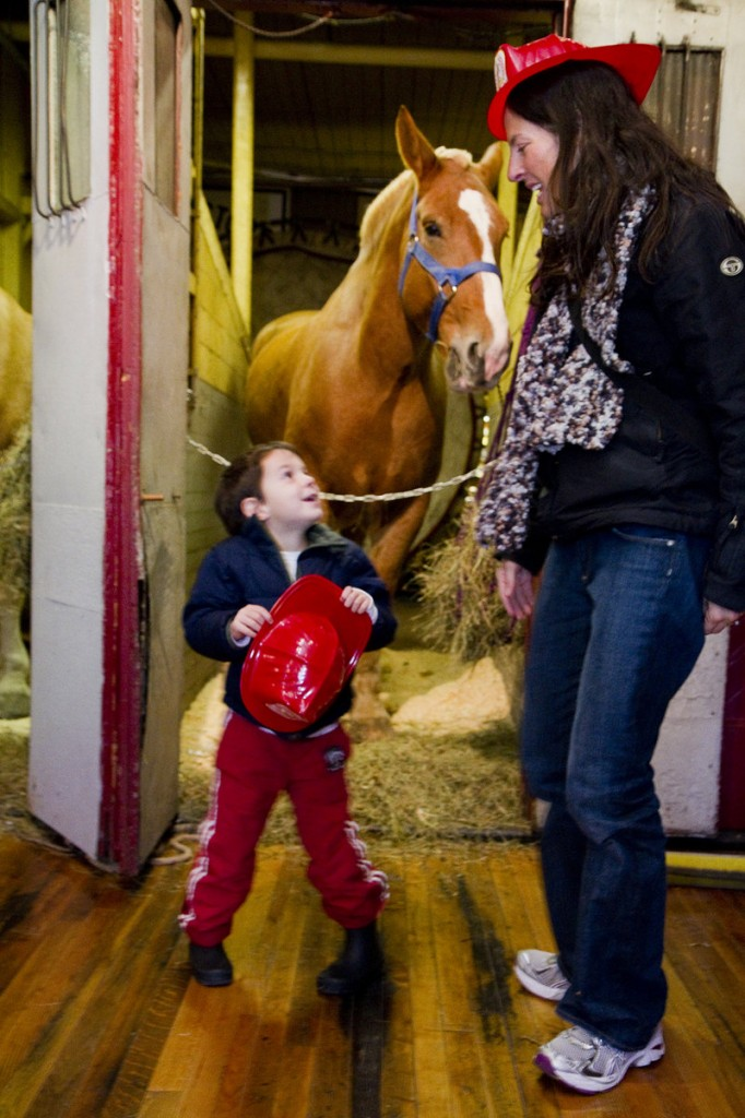 """Oscar Goss, 4, of Portland talks with his mother, Stephanie, during an open house at the Portland Fire Museum on Saturday. Oscar and his family come to the Spring Street museum often, but he likes the open house because of the """"neigh-neighs,"""" his name for the horses."""