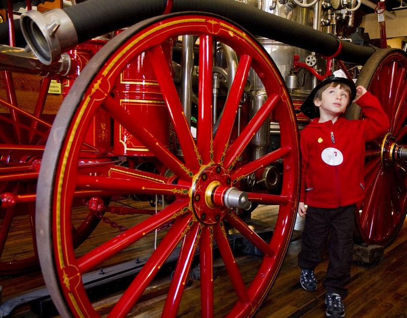 Senya Rogers-Kaufman, 5, of Portland checks out some antique firefighting equipment.