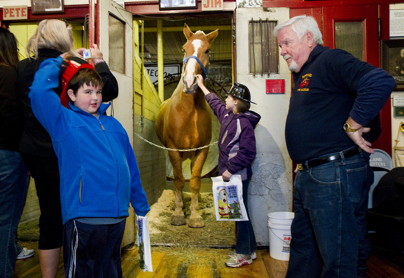 """Simon Girard, 7, of Old Orchard Beach poses questions to retired Portland firefighter John """"Smokey"""" Chandler during an open house at the Portland Fire Museum on Saturday. Alison Blow, 10, of Biddeford, pets Jim the horse."""