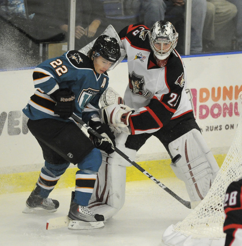 Tim Kennedy, a former Pirate who now plays for the Worcester Sharks, battles for the puck behind the night with Portland goalie Mark Visentin.