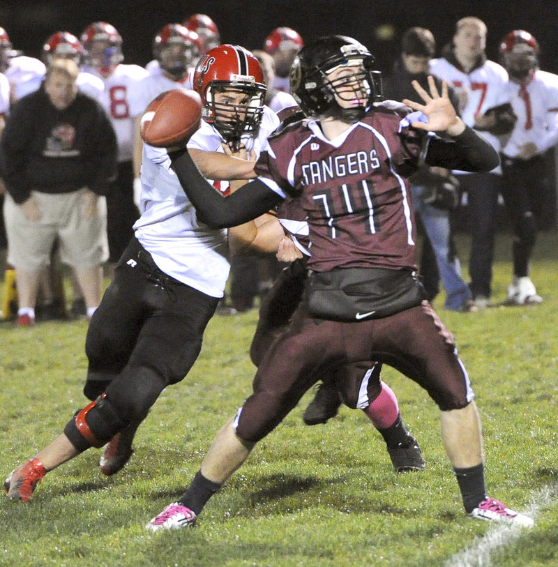 Greely quarterback Drew Hodge tries to unleash a pass as Drew Shelley of Wells closes in during Friday's Western Class B quarterfinal in Cumberland. Wells pulled out a 9-7 win.