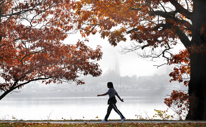CALM BEFORE THE STORM: A woman walks along Back Cove in Portland on Saturday as morning fog lingers over the city. Expect Sunday to be mostly cloudy with high temperatures in the lower 50s. The weather is expected to deteriorate Monday as Sandy arrives.