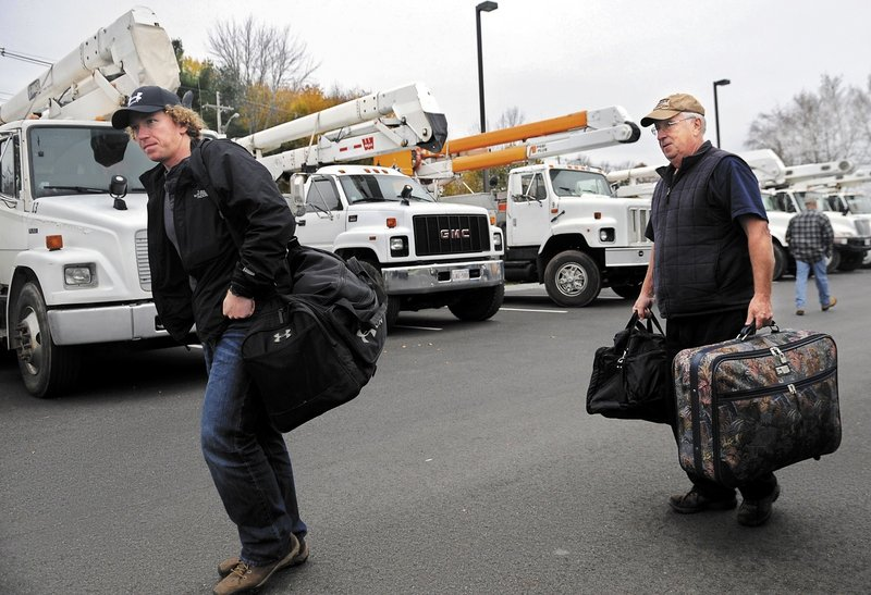 Canadian utility crews called in to help with storm recovery if needed included electrical lineman Dave Leavitt, left, shown arriving Sunday at the Hampton Inn in Augusta.