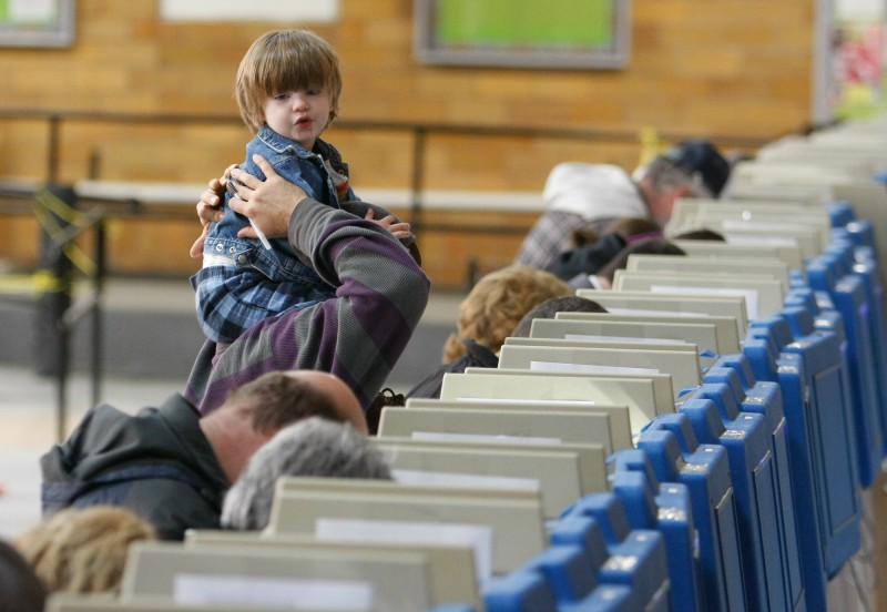 Lincoln Paquet, 2, sits atop the shoulders of Jim Giroux while voting at the J. Richard Martin Community Center in Biddeford Tuesday, November 6, 2012. Jill Brady/Staff Photographer