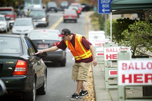 Clark County elections official Miguel Rivera takes ballots from motorists outside the Clark County Elections office Tuesday Nov. 6, 2012 in Vancouver, Wash. (AP Photo/The Columbian, Troy Wayrynen)