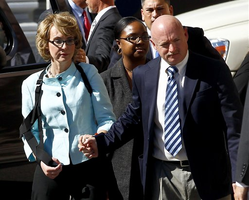 Former Democratic Rep. Gabrielle Giffords, left, and her husband Mark Kelly leave after the sentencing of Jared Loughner at U.S. District Court on Thursday in Tucson, Ariz.