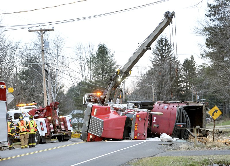 Workers try to upright a Troiano Waste Services truck on Route 237 in Gorham on Tuesday. The truck was loaded with 15 cubic yards of liquid waste chicken and raw chicken parts.Police blamed driver inattention for the crash.