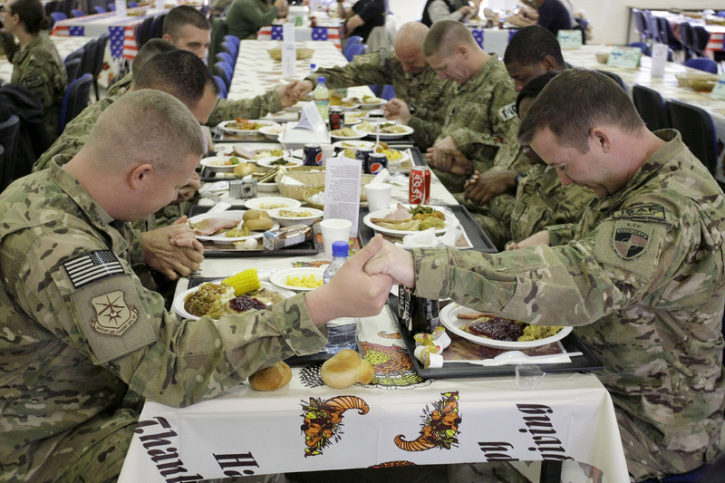 U.S. soldiers pray before eating a Thanksgiving meal at a dining hall at the U.S.-led coalition base in Kabul, Afghanistan, on Thursday.