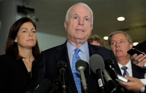 Sen. John McCain, R-Ariz., ranking Republican on the Senate Armed Services Committee, center, flanked by fellow committee members, Sen. Kelly Ayotte, R-N.H., left, and Sen. Lindsey Graham, R-S.C., right, speaks on Capitol Hill on Tuesday following a meeting with UN Ambassador Susan Rice.