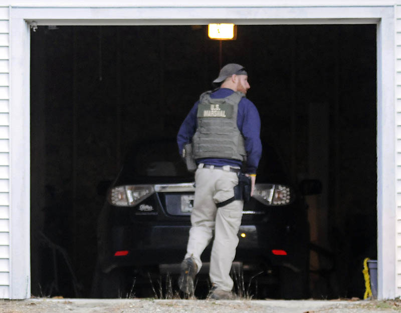 A U.S. Marshal Service investigator searches the garage at the residence of Barbara Cameron, the ex-wife of fugitive James Cameron, Tuesday in Hallowell. Authorities are continuing to hunt for Maine's former top drug prosecutor.