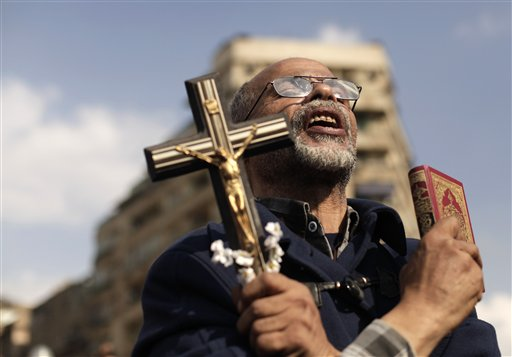 An Egyptian protester chants slogans and holds a cross and a Quran in Tahrir Square on Frida. Supporters and opponents of Egypt's Islamist President Mohammed Morsi staged rival rallies Friday after he assumed sweeping new powers, a clear show of the deepening polarization plaguing the country.