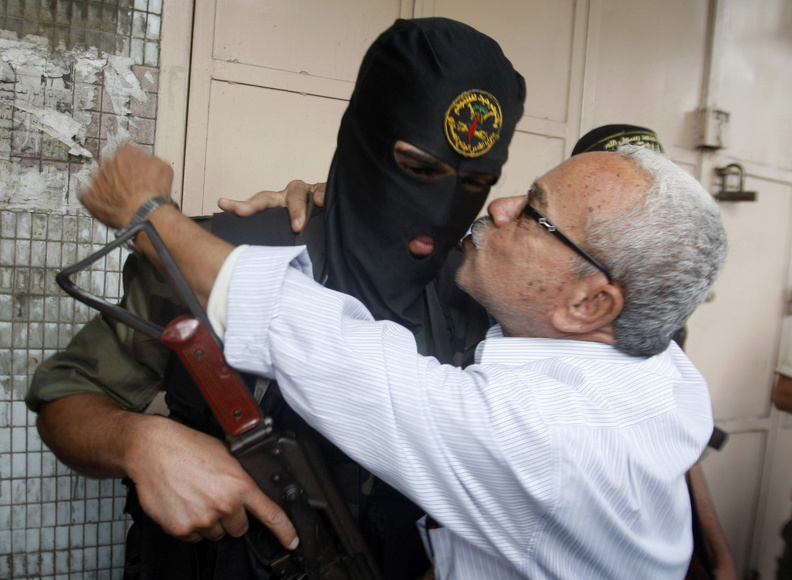 A Gaza man hugs a Palestinian militant after a press conference in Gaza City on Thursday. Gazans are celebrating a cease-fire agreement reached with Israel to end eight days of fighting.