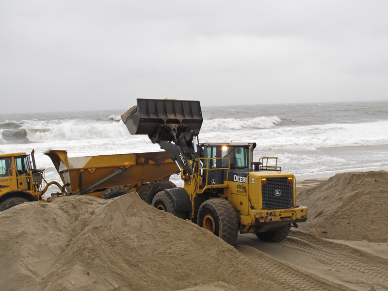 Workers use heavy equipment to hurriedly push piles of sand back onto the beach in Point Pleasant Beach, N.J., on Wednesday as a nor'easter was hitting.