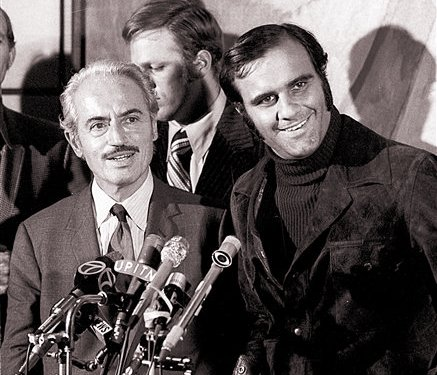 This 1972 photo shows Marvin Miller, left, executive director of the Major League Baseball Players Association, and Joe Torre, of the St. Louis Cardinals, talking to reporters after Miller announced an end to a baseball strike.