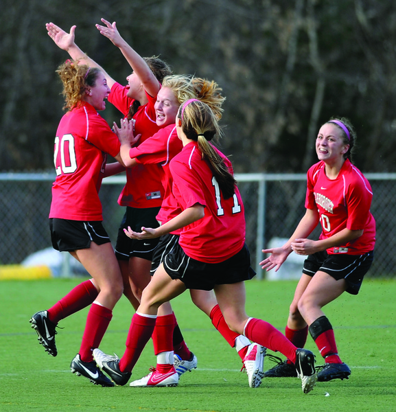 Sarah Martens raises her hands in the air and is swarmed by Scarborough teammates after scoring the winning goal in the second overtime in Saturday's Class A state championship game at Hampden. The Red Storm beat Bangor, 2-1.