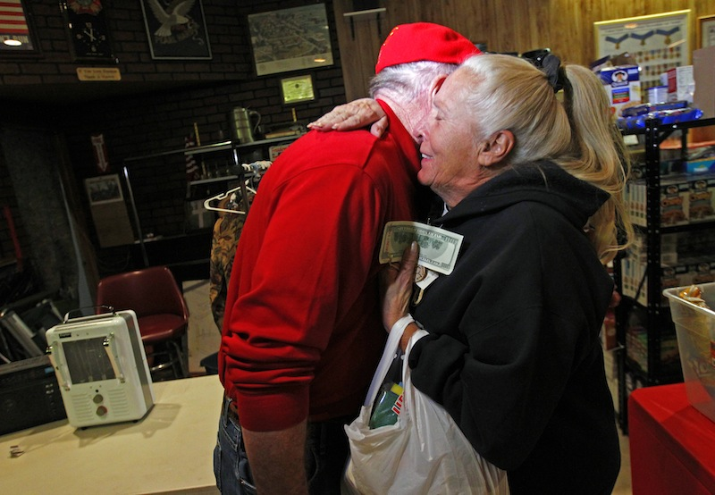 Carol Hefty hugs Secret Santa after he gave her a $100 dollar bill while she was looking for supplies at a temporary supply house at the Oakwood Heights VFW Post 9587 in the boro of Staten Island, New York, N.Y., Thursday, Nov. 29, 2012. The wealthy philanthropist from Kansas City, Mo. Secret Santa distributed $100 dollar bills to needy people at several locations in Elizabeth, N.J. and Staten Island.