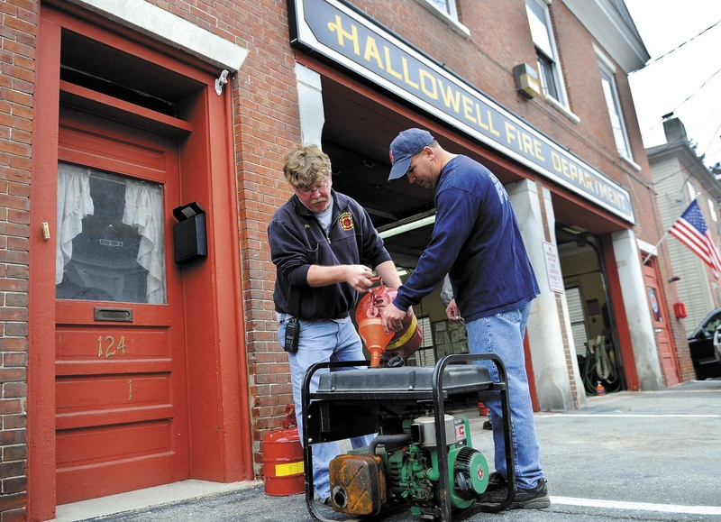 Hallowell firefighters Rick Seymour, left, and Roy Girard fuel up a generator at the city's station in preparation for the arrival of Hurricane Sandy.