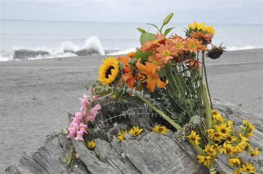 Flowers rest on a drift log yards from the breaking surf of the Big Lagoon beach near Trinidad, Calif., where a family that tried to rescue their dog were swept out to sea.