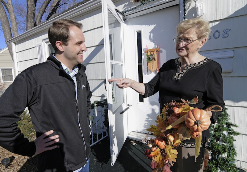 Jake Loesch and his grandmother, Bunny Arseneau pose outside Bunny's home where they replaced the Thanksgiving ornament with one for Christmas on the front door, Tuesday, Nov. 20, 2012 in Crystal, Minn. The issue dividing the family at the Thanksgiving table will be gay marriage. Although Arceneau disagreed with her grandson who was deputy communications director for Minnesotans United for All Familes which opposed Minnesota's gay marriage amendment, she congratulated her grandson on his stance. (AP Photo/Jim Mone)