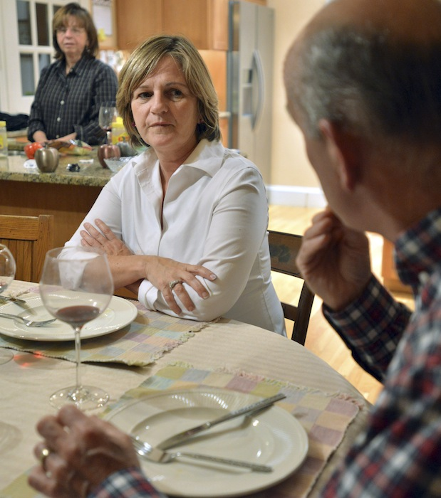 In this photo taken Friday, Nov. 16, 2012, Anne Brennan, center, of Hingham Mass., listens to her sister, Linda Marshall, rear, and brother-in-law Steve Marshall, right, discuss the recent presidential election as the family gathers for dinner in Hingham and where politics are a frequent, and divisive topic of conversation. (AP Photo/Josh Reynolds)