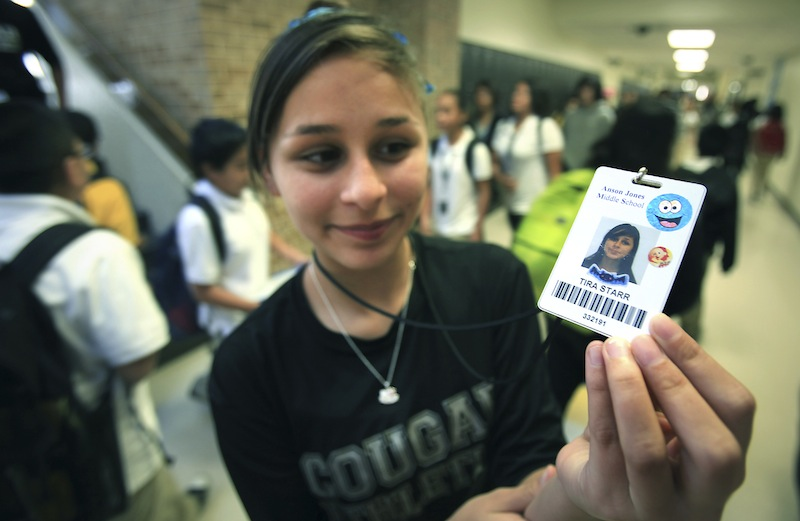 In this Oct. 1, Tira Starr, an 8th grader at Anson Jones Middle School, shows her ID badge as students change classes in San Antonio, Texas. The San Antonio school district's website was hacked over the weekend to protest its policy requiring students to wear microchip-embedded cards tracking their every move on campus. A teenager purportedly working with the hacker group Anonymous said in an online statement that he took the site down because the Northside school district