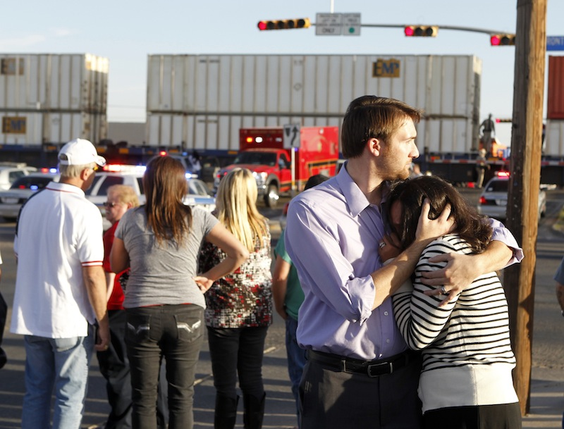 Bystanders react as emergency personnel work the scene where a trailer carrying wounded veterans in a parade was struck by a train in Midland, Texas, Thursday, Nov. 15, 2012.
