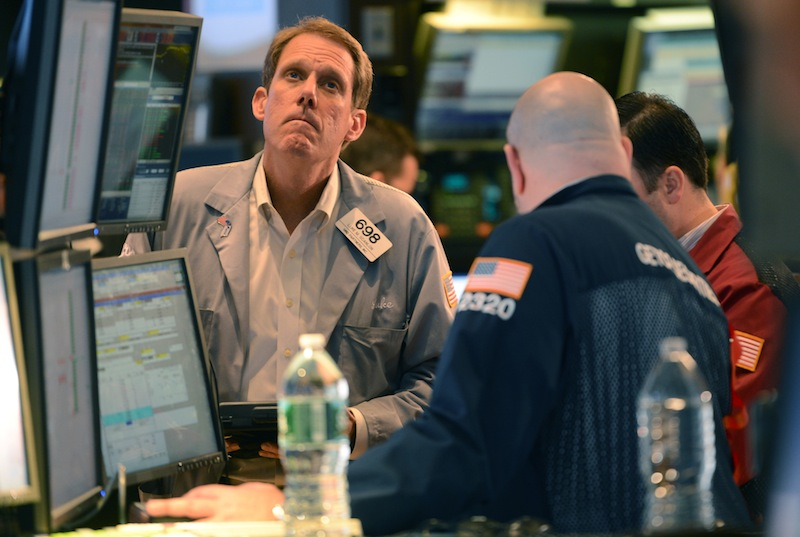 Luke Scanlon, left, of MND Partners Inc. works on the floor of the New York Stock Exchange the day after Pres. Barack Obama was re-elected, Wednesday, Nov. 7, 2012 in New York. With President Barack Obama elected to another term, U.S. investors dumped stocks Wednesday and turned their focus to a world of problems, including a