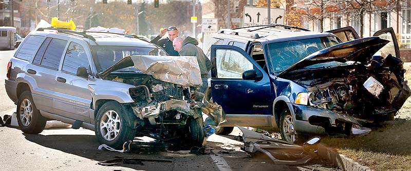 Police officers investigate a head-on collision on Marginal Way in Portland Sunday. The crash sent all 10 of the two vehicles' occupants to hospitals with numerous injuries, police said.