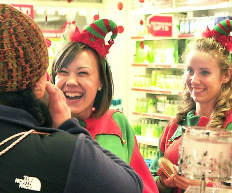 Customer Kari Turgeon, left, smells a candle as she is waited on by a pair of Bath & Bodyworks clerks dressed as elves at at 5:47 Friday morning in the Marketplace at Augusta. Alexis Saucier, center, said that she was Hermie the elf, while co-worker Stephanie Smith's nametag read Buddy.