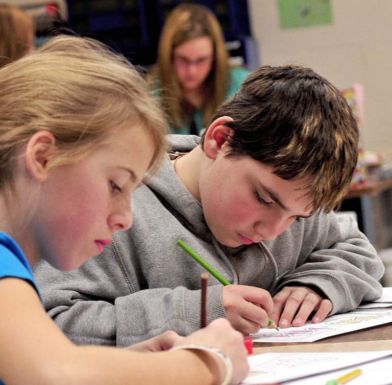 Cornville Regional Charter School students Annie Cooke and Isaiah Cole work on papers as teacher Ashley Leslie, in back, helps another student recently.
