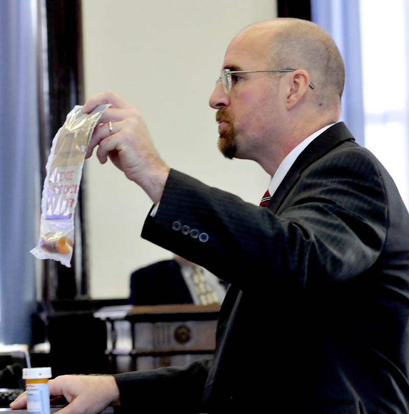 Assistant Attorney General Don Macomber holds a bag filled with prescription drugs in his opening statement against defendant Robert Nelson, on trial in the death of Everett Cameron in Skowhegan Superior Court, on Monday.